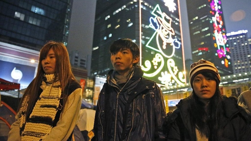 Three students, from right, Prince Wong, Joshua Wong and Isabella Lo walk at the occupied area outside government headquarters during their hunger strike in Hong Kong Wednesday, Dec.3, 2014. A prominent Hong Kong teen protest leader said he's going on a hunger strike after a failed attempt by pro-democracy activists to step up their flagging movement for democratic reforms by surrounding government headquarters. (AP Photo/Kin Cheung)