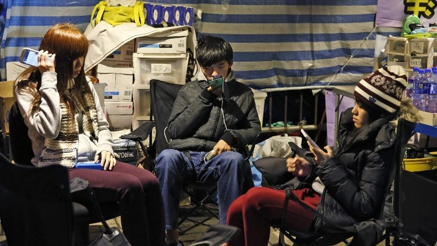 Three students, from right, Prince Wong, Joshua Wong and Isabella Lo use their smart phones inside their tent at the occupied area outside government headquarters during their hunger strike in Hong Kong Wednesday, Dec. 3, 2014. A prominent Hong Kong teen protest leader said he's going on a hunger strike after a failed attempt by pro-democracy activists to step up their flagging movement for democratic reforms by surrounding government headquarters. (AP Photo/Kin Cheung)