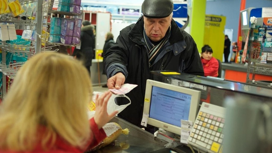 A customer pays with cash in a supermarket in Donetsk, eastern Ukraine, Thursday, Dec. 4, 2014. Since Dec. 1 local residents haven't been able to use bank cards in Donetsk as the Ukrainian government decided to shut down the banking system in the rebel-held southeast. ATMs have not been working for about a month, having run out of cash. (AP Photo/Balint Szlanko)