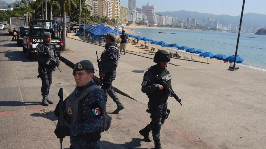 Mexican federal police stand guard in the main seaside avenue of Acapuclo in the state of Guerrero, Mexico, Thursday Dec. 4, 2014, ahead of the arrival of Mexico President Enrique Pena Nieto. Under very heavy security, President Pena Nieto visited the tumultuous southern state of Guerrero for the first time since 43 college students disappeared there more than two months ago, provoking the greatest crisis of his presidency. (AP Photo/Bernandino Hernandez)