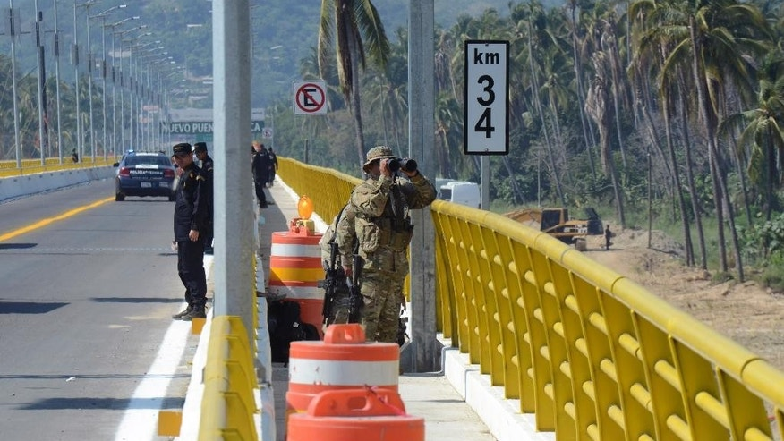 Police and army guard the newly built Coyuca bridge near the town of Coyuca de Benitez in the state of Guerrero, Mexico, Thursday Dec. 4, 2014, ahead of the arrival of Mexico President Enrique Pena Nieto. Under very heavy security, President Pena Nieto visited the tumultuous southern state of Guerrero for the first time since 43 college students disappeared there more than two months ago, provoking the greatest crisis of his presidency. (AP Photo/Bernandino Hernandez)
