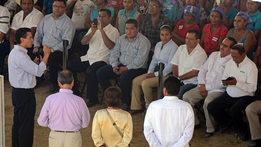 Mexico's President Enrique Pena Nieto, left, speaks to the audience in the town of Coyuca de Benitez in the state of Guerrero, Mexico, Thursday Dec. 4, 2014. Under very heavy security, President Pena Nieto visited the tumultuous southern state of Guerrero for the first time since 43 college students disappeared there more than two months ago, provoking the greatest crisis of his presidency. (AP Photo/Bernandino Hernandez)