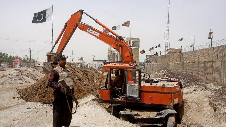 In this May, 16, 2014 photo, a Pakistani border guard stands alert as an excavator digs a trench along the Pakistan Afghanistan border at Chaman post in Pakistan. Like the Berlin Wall or Israel's West Bank barrier, the planned 485-kilometer (300-mile) trench is giving physical form to a border that locals have long seen as artificial, dividing families and crippling trade. And it is adding to simmering tensions between Afghanistan and Pakistan, U.S. allies which have long accused each other of turning a blind eye to insurgents. (AP Photo/Matiuallah Achakzai)