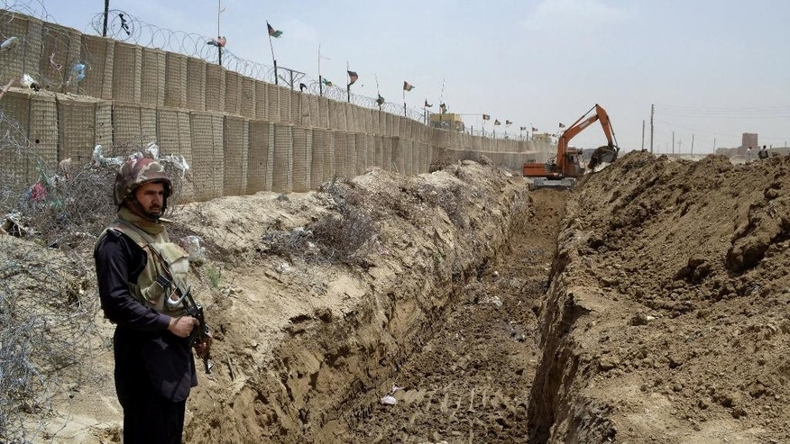 In this May, 16, 2014 photo, a Pakistani border guard stands alert as an excavator digs a trench along Pakistan Afghanistan border at Chaman post in Pakistan. ILike the Berlin Wall or Israel's West Bank barrier, the planned 485-kilometer (300-mile) trench is giving physical form to a border that locals have long seen as artificial, dividing families and crippling trade. And it is adding to simmering tensions between Afghanistan and Pakistan, U.S. allies which have long accused each other of turning a blind eye to insurgents. (AP Photo/Matiuallah Achakzai)