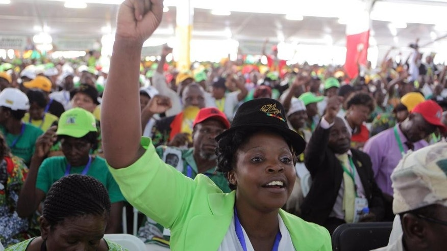 A supporter of Zimbabwean President Robert Mugabe chants the party slogan during the official opening of the  Zanu pf 6th National Congress in Harare, Thursday, December, 4, 2014. Mugabe attacked his deputy President Joice Mujuru aledging she plotted to remove him from power.(AP Photo/Tsvangirayi Mukwazhi)