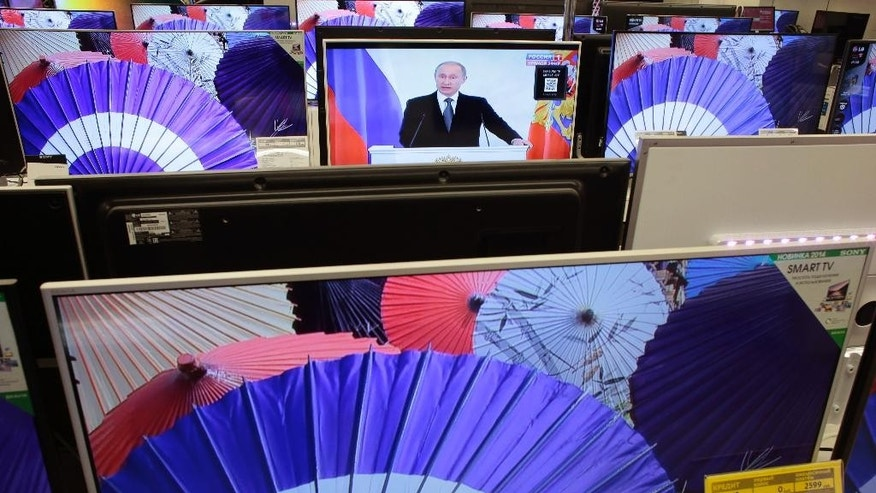 Russian President Vladimir Putin is seen on a TV screen at a shop in Moscow, Russia, on Thursday, Dec. 4, 2014, giving his annual state of the nation address in the Kremlin. Russian President Vladimir Putin has defended the Kremlin's aggressive foreign policy, saying the actions are necessary for his country's survival.  (AP Photo/Ivan Sekretarev)