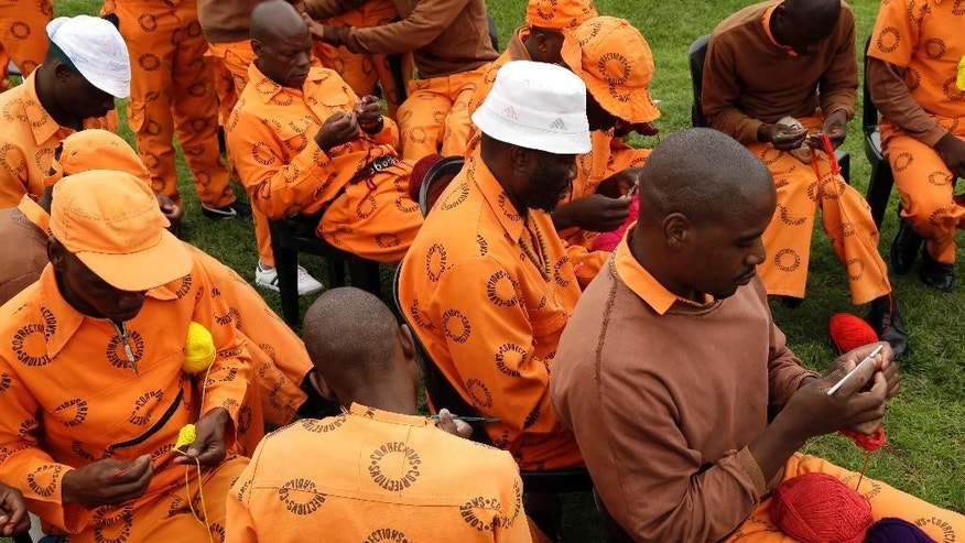 In this photo taken Tuesday, Nov. 27, 2014  prisoners in orange jumpsuits, at the Zonderwater prison east of Pretoria, South Africa, crochet blankets. The prisoners  craft the brightly colored blankets  for charity as part of a memorial to South Africa's former president Nelson Mandela on the first anniversary of his death. (AP Photo/Themba Hadebe)