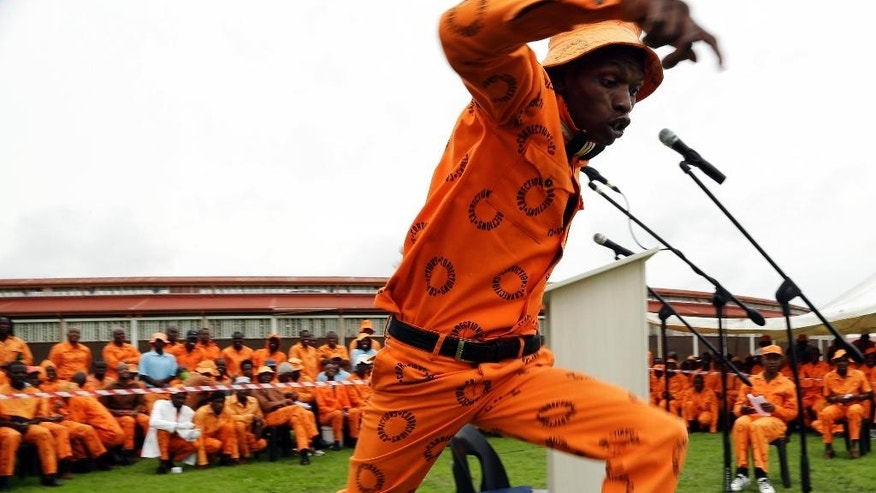 In this photo taken Tuesday, Nov. 27, 2014, a prisoner entertains inmates at the Zonderwater prison east of Pretoria, South Africa, during a break in a crochet session. The prisoners  craft brightly colored blankets  for charity as part of a memorial to South Africa's former president Nelson Mandela on the first anniversary of his death. (AP Photo/Themba Hadebe)