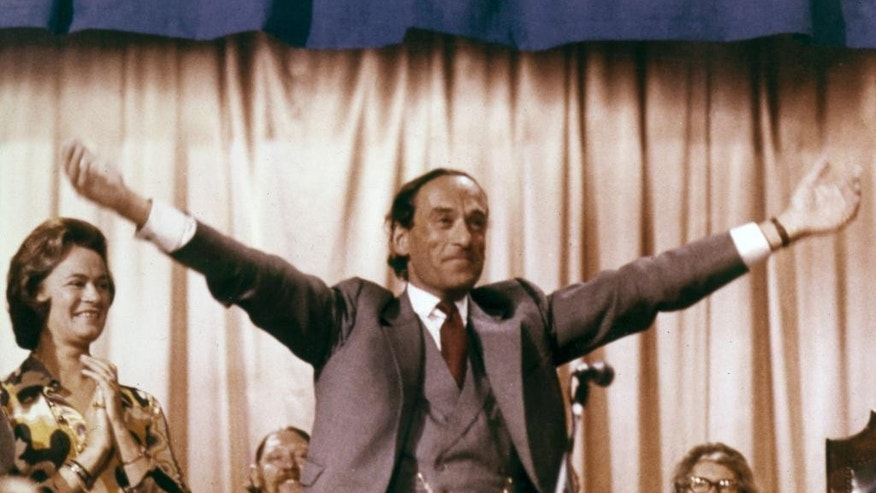 FILE - In this file photo dated Sept. 22, 1973, Jeremy Thorpe, Liberal Party leader spreads his arms, responding to a standing ovation at the end of the Liberal Party's annual conference at Southport, England, with Thorpe's wife Marion, the former Countess of Harewood, left.  It is announced Thursday Dec. 2014, that Thorpe has died aged 85. Tributes have been paid to former Liberal Party leader Thorpe, who fought for investment in his beloved North Devon area of England, and against apartheid in South Africa, but his political career was ended by a court case and alleged homosexual relationship, which was illegal at the time.  (AP Photo/Lawrence Harris, FILE)