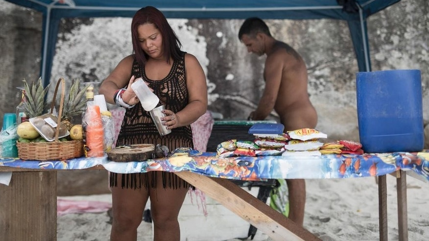 Erica Menezes de Oliveira prepares a drink as her husband Carlos Eduardo grabs some ice on Abrico beach, recently designated as nudist after a 20-year-battle, in Rio de Janeiro, Brazil, Thursday, Dec. 4, 2014. The city renown worldwide for its wild Carnival celebrations featuring near-naked samba dancers has finally gotten its first official nudist beach. (AP Photo/Felipe Dana)