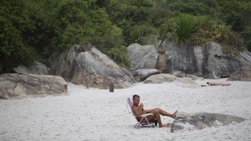 "Carlos Eduardo sunbathes on Abrico beach, recently designated as nudist after a 20-year-battle, in Rio de Janeiro, Brazil, Thursday, Dec. 4, 2014. The beach has been attracting nudists since the late 1950's in defiance of legal charges including ""offending public morals."" With the new law, nudists are freed from any threat of legal action and provides increased protection. (AP Photo/Felipe Dana)"