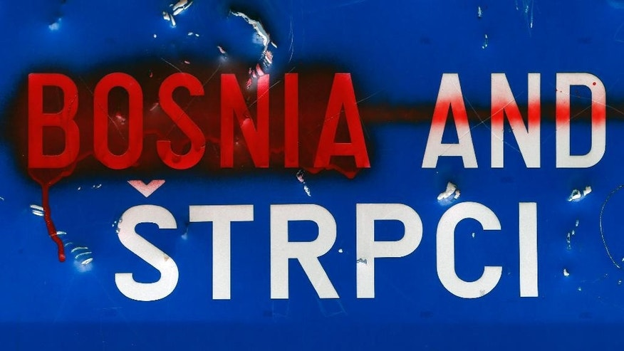 "In this photo taken Thursday, July 17, 2014, a damaged traffic sign reads: ""Bosnia and Strpci"" at railway station near the village of Strpci, eastern Bosnia. Official documents released by the state railway company showed that Yugoslavia's authorities had been warned in advance that the abduction would take place, but still failed to act to prevent it. Railway security officials held meetings with the police, the state security and the defense ministry seeking protection for its trains and passengers from the Bosnian Serb soldiers, who, they said, would stop the train in Bosnia. At the time, the Yugoslav military was in charge of guarding the entire railway - including the nearly 10 kilometer (6 mile) stretch passing through the Bosnian territory. Additional attention was necessary as a similar bus abduction of 17 Muslims had taken place in October 1992- once again by Lukic's group - as well as several smaller incidents. (AP Photo/Darko Vojinovic)"