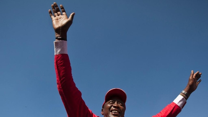 FILE - In this Saturday, March 2, 2013 file photo, Kenya's then Presidential candidate Uhuru Kenyatta waves to the crowd from the sunroof of his vehicle as he arrives for the final election rally of The National Alliance party at Uhuru Park in Nairobi, Kenya. The International Criminal Court's chief prosecutor dropped all crimes against humanity charges against Kenya's president Uhuru Kenyatta on Friday, Dec. 5, 2014 highlighting the court's problems in bringing to justice the high-ranking officials it has accused of atrocities. (AP Photo/Ben Curtis, File)