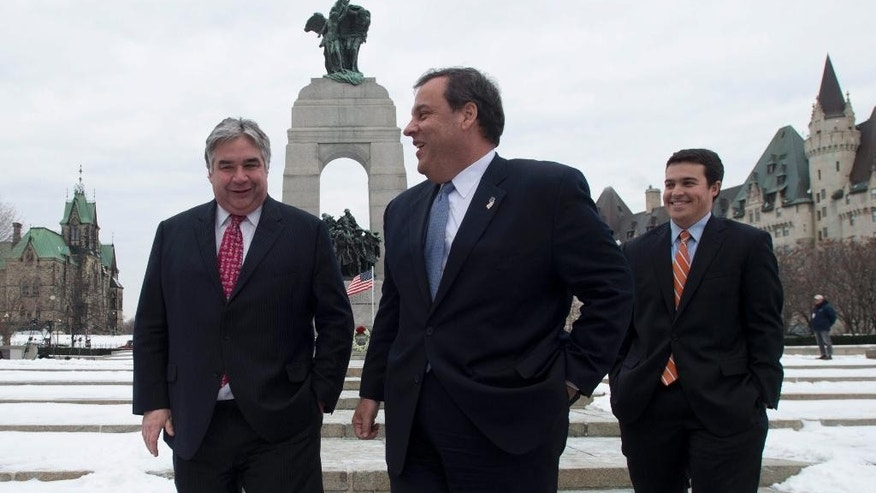 Government House Leader Peter Van Loan speaks with New Jersey Governor Chris Christie and his son Andrew after they paid a visit to the National War Memorial in Ottawa, Friday, Dec. 5, 2014.  (AP Photo/The Canadian Press, Adrian Wyld)