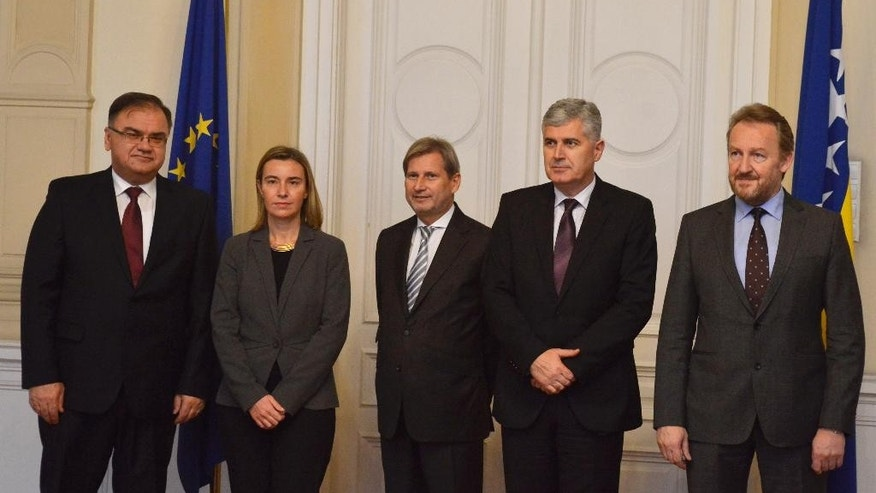 Federica Mogherini, second left, EU High Representative for Foreign Affairs and Security Policy/Vice-President of the European Commission and Johannes Hahn, center, European Commissioner for European Neighborhood Policy and Enlargement Negotiations pose for the media with Mladen Ivanic, left, Serb member and chairman of Bosnian tripartite Presidency, Dragan Covic, second right, Croatian member of Bosnian tripartite Presidency and Bakir Izetbegovic, Muslim member of Bosnian tripartite Presidency in Sarajevo on Friday Dec. 5, 2014. Federica Mogherini accompanied by Johannes Hahn, European Commissioner for European Neighborhood Policy and Enlargement Negotiations is on a one day visit to Bosnia to discuss reforms in Bosnia for EU integration. (AP Photo/Sulejman Omerbasic)