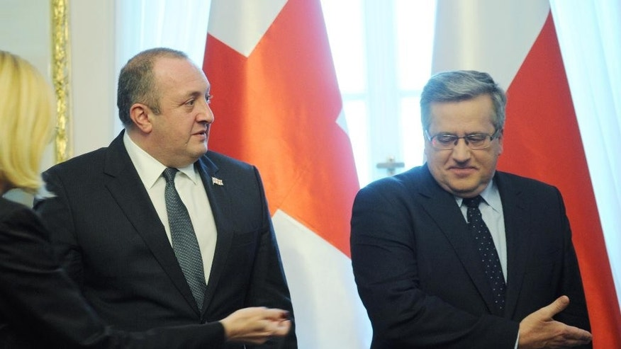 Polish Bronislaw Komorowski, right, and his assistant, far left, show the way to President of Georgia Giorgi Margvelashvili before talks in the Belweder Palace in Warsaw, Poland, Thursday, Dec. 4, 2014. Margvelashvili came to Poland for a working visit. (AP Photo/Alik Keplicz)