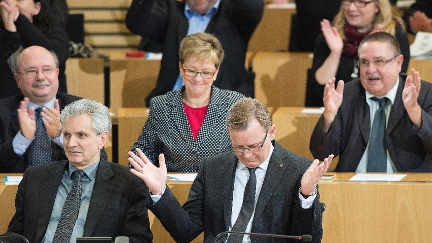 Bodo Ramelow, front right, accepts applause after his election to the first state governor from the party 'Die Linke' (The Left) in a German state at the regional parliament of Thuringia in Erfurt, Germany, Friday, Dec. 5, 2014. Ramelow is now head of a three-party coalition with a single-seat majority. (AP Photo/Jens Meyer)