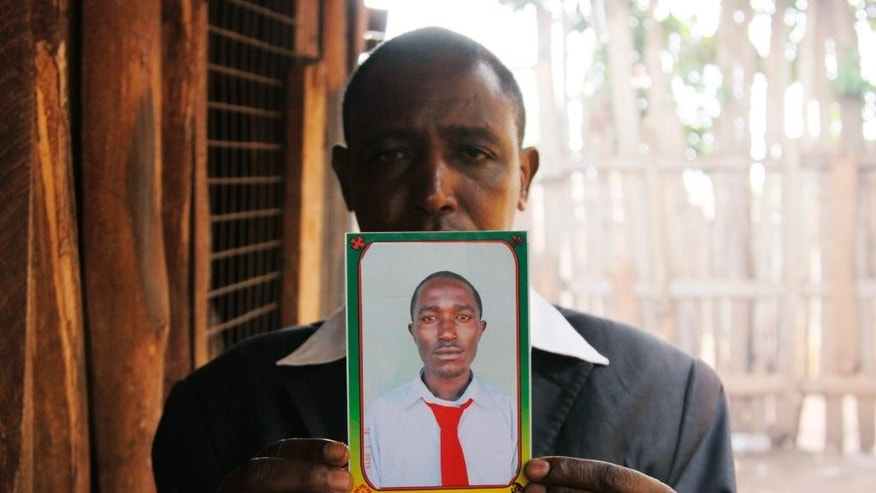 In this May 9, 2014 photo, Mohammed Karanja displays a photograph of his son Yusuf Mohamed as he speaks to The Associated Press in Nyeri, Kenya. Yusuf Mohamed's body and those of four of his friends were discovered April 17 with bullet holes in their heads deep in a forest near the central Kenyan town of Nyeri. The last time the five were seen was in police custody according to their families. (AP Photo/Khalil Senosi)