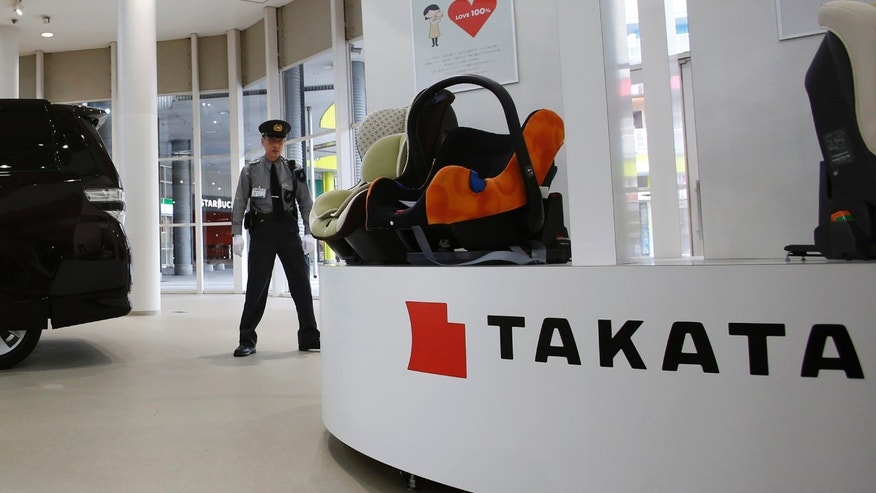 Nov. 6, 2014: A security guard stands by child seats, manufactured and displayed by Takata Corp. at an automaker's showroom in Tokyo.