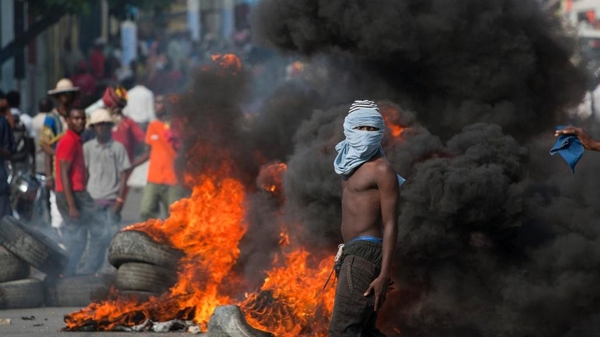 A masked anti-government demonstrator stands by burning tires during a protest demanding the resignation of Haiti's President Michel Martelly in Port-au-Prince, Haiti, Friday, Dec. 5, 2014. (AP Photo/Dieu Nalio Chery)