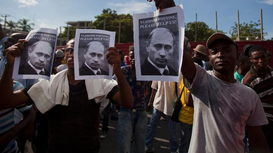 "Anti-government demonstrators hold up ""help"" signs directed at Russia's President Vladimir Putin as they demand the resignation of Haiti's President Michel Martelly in Port-au-Prince, Haiti, Friday, Dec. 5, 2014. (AP Photo/Dieu Nalio Chery)"