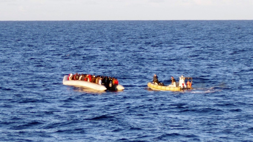 Dec. 4, 2014 -  Rescue crew on a dinghy, right, approaches migrants on a boat some 40 miles from the Libyan capital, Tripoli. Rescue crews discovered 17 bodies in a migrant boat off Libya, the first reported deaths since the European Union took over Mediterranean rescue operations, the Italian navy said Friday.