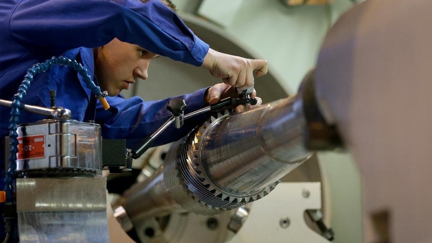 In this Dec. 2, 2014 picture Jan Nowak, employee of the VAKOMA company, works on a machine in Magdeburg, Germany.  VAKOMA produces heavy gear drives and drive systems for turbo compressors as well as mills and kilns for the cement industry. (AP Photo/Michael Sohn)