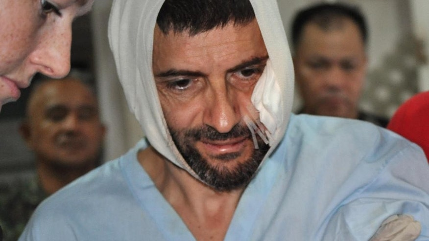 Swiss hostage Lorenzo Vinciguerra, is treated in a hospital following his daring escape from the hands of the Muslim Abu Sayyaf extremists, in Jolo in southern Philippines, Saturday, Dec. 6, 2014. Vinciguerra, who has been a hostage for two years, made a dramatic escape Saturday from Abu Sayyaf extremists when he hacked a rebel commander then got shot as he dashed to freedom amid a military artillery assault, ending more than two years of jungle captivity in the southern Philippines, officials said. (AP Photo/Nickee Butlangan)