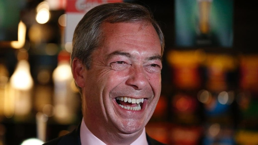 "FILE - In this Friday, May 23, 2014 file photo, Nigel Farage, leader of Britain's United Kingdom Independence Party (UKIP) smiles at a pub in South Benfleet, England. British politician Nigel Farage has defended a hotel that insisted a breast-feeding mother cover up, suggesting women might ""sit in the corner"" while they feed their babies. Farage told LBC radio Friday Dec. 5, 2014 that women should breast-feed ""in a way that is not openly ostentatious."" (AP Photo/Lefteris Pitarakis, File)"
