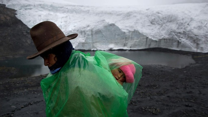 Fausta Ortiz, 38, Pastoruri's glacier guardian, stands guard while carrying her daughter Lisoyun, 2, in Huaraz, Peru, Thursday, Dec. 4, 2014. According to Alejo Cochachin, coordinator of the glaciology unit, the Pastoruri glacier retreated 576 meters between 1980 and 2014. Peru's glaciers have lost more one-fifth of their mass in just three decades, and the 70 percent Peru's 30 million people who inhabit the country's Pacific coastal desert, depend on glacial runoff for hydropower and to irrigate crops, meaning their electricity and long-term food security could also be in peril. Higher alpine temperatures are killing off plant and animal species in cloud forests and scientists predict Pacific fisheries will suffer. (AP Photo/Rodrigo Abd)