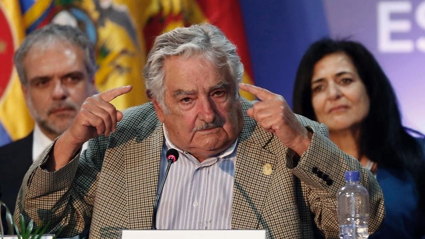 ALTERNATIVE CROP OF DOR115 - New UNASUR President  Jose Mujica, President of Uruguay, left, speaks during the UNASUR summit in Guayaquil, Ecuador, Thursday, Dec. 4, 2014. Mujica is reiterating his willingness to resettle six Guantanamo prisoners in his country while calling on the United States to end its decades-old embargo against Cuba. Mujica's open letter to President Barack Obama appeared Friday on his presidency website. (AP Photo/Dolores Ochoa)