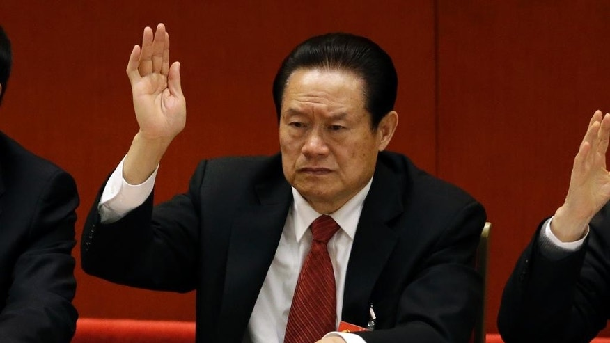 FILE - In this Wednesday Nov. 14, 2012 file photo, Zhou Yongkang, the then Chinese Communist Party Politburo Standing Committee member in charge of security, raises his hand to show approval for a work report during the closing ceremony for the 18th Communist Party Congress at the Great Hall of the People in Beijing, China. China's official Xinhua News Agency says the country's former security chief, Zhou Yongkang, has been expelled from the Communist Party. Xinhua said the decision was made Friday Dec. 5, 2014 at a meeting of the Political Bureau of the party's Central Committee. (AP Photo/Lee Jin-man, File)