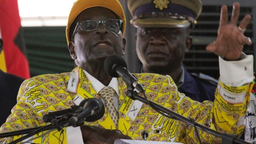 Zimbabwean President Robert Mugabe delivers his speech during the official opening of the  Zanu pf 6th National Congress in Harare, Thursday, Dec. 4, 2014. Mugabe attacked his deputy President Joice Mujuru aledging she plotted to remove him from power.(AP Photo/Tsvangirayi Mukwazhi)