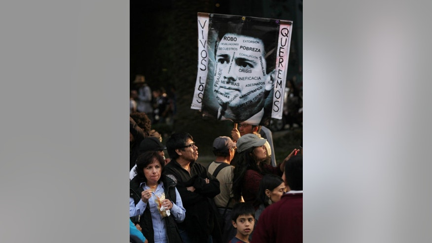 "A protester holds a defaced image of Mexico's President Enrique Pena Nieto that reads in Spanish ""We want them alive"" during a demonstration against the disappearance of 43 students from the Isidro Burgos rural teachers college in Mexico City, Saturday, Dec. 6, 2014.  At least one of the college students missing since September has been identified among charred remains found near a garbage dump, two Mexican officials confirmed Saturday. A family member of a missing student told The Associated Press that the remains were of Alexander Mora. The students went missing Sept. 26 after confrontations with police in Iguala, in southern Guerrero state, that killed three students and three bystanders. (AP Photo/Marco Ugarte)"
