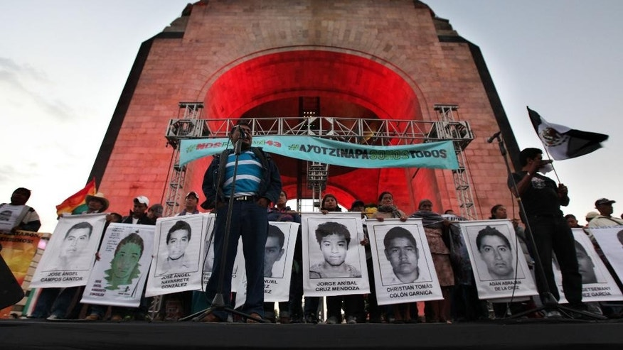 Felipe de la Cruz, the father of one of the 43 missing students from the Isidro Burgos rural teachers college, speaks to a crowd in front of other relatives holding posters of their missing loved ones, during a protest at the Revolution Monument in Mexico City, Saturday, Dec. 6, 2014. At least one of the college students missing since September has been identified among charred remains found near a garbage dump, two Mexican officials confirmed Saturday. A family member of a missing student told The Associated Press that the remains were of Alexander Mora. The students went missing Sept. 26 after confrontations with police in Iguala, in southern Guerrero state, that killed three students and three bystanders. (AP Photo/Marco Ugarte)