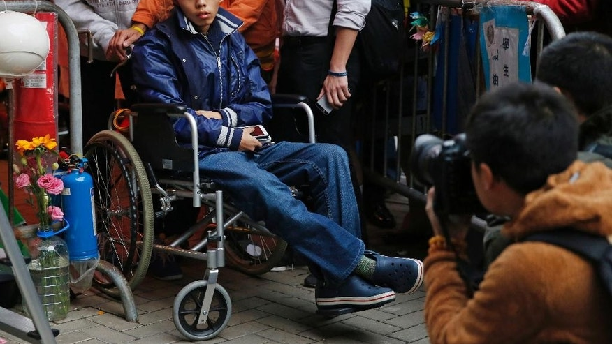 FILE - In this Dec. 5, 2014 file photo, student leader Joshua Wong attends a news conference as he sits on a wheel chair during a hunger strike at the occupied area outside government headquarters in Hong Kong. The prominent teenage leader of Hong Kong's pro-democracy protests ended his hunger strike Saturday, Dec. 6 after 4 1/2 days at his doctor's urging. (AP Photo/Kin Cheung, File)