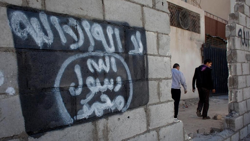 "In this photo taken Oct. 28, 2014, two Jordanian men walk past graffiti depicting the flag of the Islamic State group with Arabic that reads, ""There is only one God and Muhammad is his prophet,"" in the city of Ma'an, Jordan.  Local authorities quickly stripped away public signs of support for the Islamic State group in this desert town. Black flags have been removed from rooftops. Graffiti proclaiming the extremists' imminent victory have been whitewashed. But supporters of the Middle East's most radical extremist group are only laying low. Support for the Islamic State group is this vital U.S. ally, pulling support from Jordanians bitter over poverty and disenfranchisement. ""I don't expect 2015 to pass peacefully,"" (AP Photo/Nasser Nasser)"