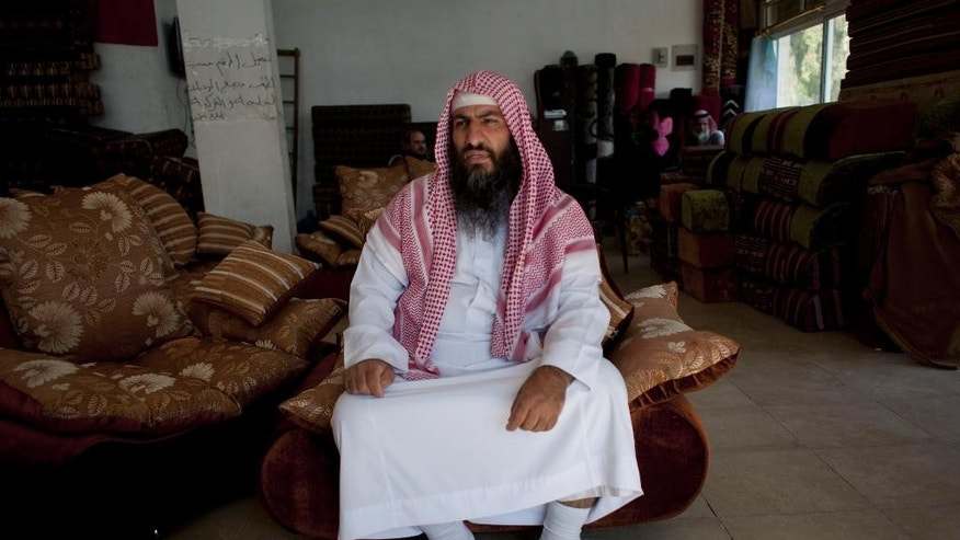 "In this photo taken Oct. 29, 2014, Salafi cleric Mohammed al-Shalabi, 48, widely known as Abu Sayyaf, talks during an interview with the Associated Press at a furniture store, owned by the head of Abu Sayyaf's clan, in the city of Ma'an, Jordan.  Local authorities quickly stripped away public signs of support for the Islamic State group in this desert town. Black flags have been removed from rooftops. Graffiti proclaiming the extremists' imminent victory have been whitewashed. But supporters of the Middle East's most radical extremist group are only laying low. Support for the Islamic State group is this vital U.S. ally, pulling support from Jordanians bitter over poverty and disenfranchisement. ""I don't expect 2015 to pass peacefully,"" (AP Photo/Nasser Nasser)"