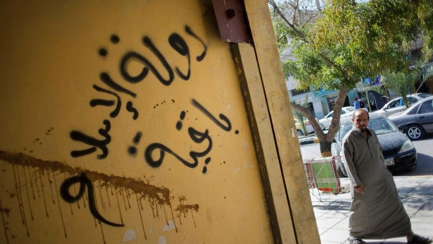 "In this photo taken Oct. 28, 2014, a Jordanian man walks past graffiti in Arabic that reads, ""the Islamic state is staying,"" in the city of Ma'an, Jordan.  Local authorities quickly stripped away public signs of support for the Islamic State group in this desert town. Black flags have been removed from rooftops. Graffiti proclaiming the extremists' imminent victory have been whitewashed. But supporters of the Middle East's most radical extremist group are only laying low. Support for the Islamic State group is this vital U.S. ally, pulling support from Jordanians bitter over poverty and disenfranchisement. ""I don't expect 2015 to pass peacefully,"" (AP Photo/Nasser Nasser)"