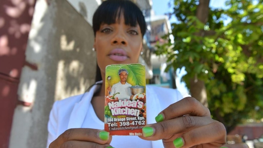 In this April 15, 2014 photo, Shackelia Jackson-Thomas holds up a business card decorated with a photo her late brother Nakiea Jackson who was fatally shot by police outside of his small restaurant, in Kingston, Jamaica. Jackson-Thomas' brother is one of over 2,000 citizens killed by police in the last decade. Rights groups long accused the government of fostering a culture of impunity by protecting law enforcers accused of killing suspects rather than subjecting them to the backlogged, inefficient court system. Activists are now cautiously hopeful the tide might be starting to turn. (AP Photo/David McFadden)