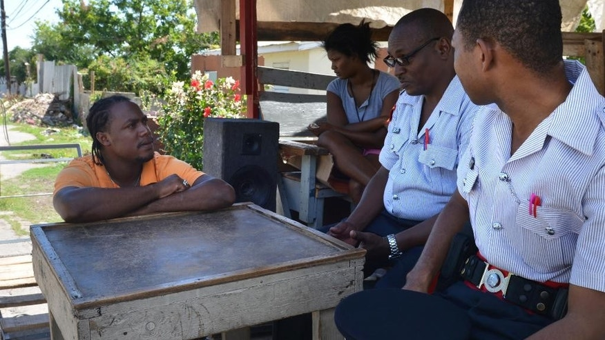 In this Nov. 25, 2014 photo, Sgt. Wickham Campbell, second from right, and Constable Jerome James, right, visit with a resident concerning security in his Rockfort neighborhood of Kingston, Jamaica. Jamaican police have often been viewed with suspicion and fear, routinely accused of indiscriminately using their weapons and intentionally killing suspects as the island struggled with soaring violent crime. Now, with overall violence ebbing, the Caribbean country is on track to have the fewest deaths at the hands of law enforcement in years, drawing cautious praise from human rights activists and making officers more welcome in some of Jamaica's grittiest districts.  (AP Photo/David McFadden)