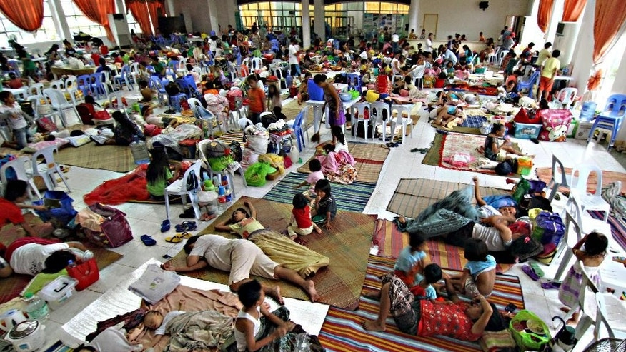 Hundreds of residents take shelter inside the provincial capitol of Surigao city close to central Philippines on Friday, Dec. 5, 2014 in anticipation of typhoon Hagupit which is expected to hit land Saturday afternoon. A wide swath of the Philippines, including the capital Manila, braced Friday for a dangerously erratic and powerful typhoon approaching from the Pacific, about a year after the country was lashed by Typhoon Haiyan that left more than 7,300 people dead. (AP Photo/Erwin Mascarinas)