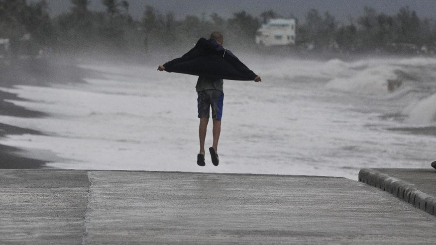 A resident jumps as he watches strong waves crash into shore as an effect of Typhoon Hagupit in Legazpi, Albay province, eastern Philippines on Sunday, Dec. 7, 2014. Typhoon Hagupit knocked out power in entire coastal provinces, mowed down trees and sent more than 650,000 people into shelters before it weakened Sunday, sparing the central Philippines a repetition of unprecedented devastation by last year's storm. (AP Photo/Aaron Favila)