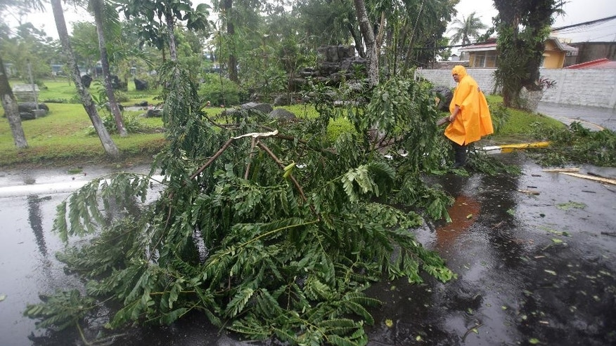 Motorists pass by toppled electrical posts due to strong winds brought by Typhoon Hagupit in Camalig, Albay province, eastern Philippines on Sunday, Dec. 7, 2014. Typhoon Hagupit knocked out power in entire coastal provinces, mowed down trees and sent more than 650,000 people into shelters before it weakened Sunday, sparing the central Philippines a repetition of unprecedented devastation by last year's storm.(AP Photo/Aaron Favila)