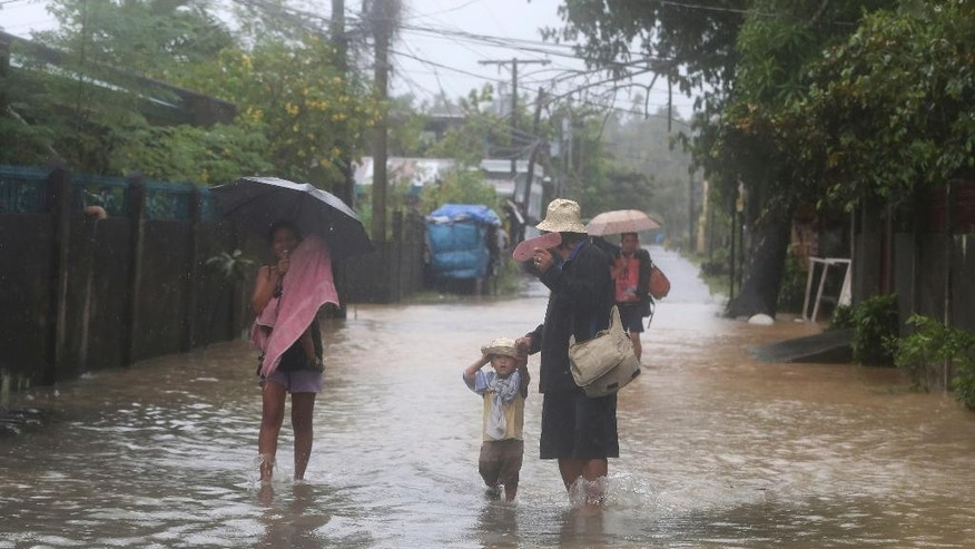 A family walks along a flooded street during a heavy rain brought by Typhoon Hagupit in Legazpi, Albay province, eastern Philippines on Sunday, Dec. 7, 2014. Haunted by Typhoon Haiyan's massive devastation last year, more than 600,000 people fled Philippine villages and the military went on full alert Saturday to brace for a powerful storm only hours away from the country's eastern coast. (AP Photo/Aaron Favila)