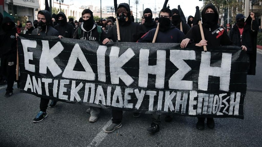 "Masked youths hold a banner that reads in Greek "" revenge"" during a protest in central Athens, on Saturday, Dec. 6, 2014. Thousands of protesters gathered to mark the sixth anniversary of the fatal police shooting of an unarmed teenager in the Greek capital that led to widespread rioting. This year's anniversary marches come as nearly nightly violent protests by supporters of one of Grigoropoulos' friends, jailed anarchist and convicted bank robber Nikos Romanos. He is on hunger strike demanding prison leave to attend lectures after he passed university entrance exams. (AP Photo/Petros Giannakouris)"