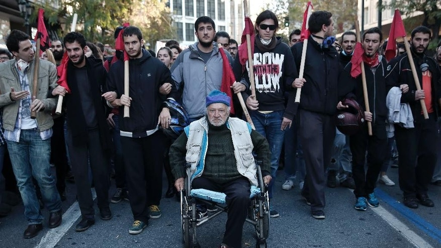 A man in a wheelchair takes part in a protest in central Athens, Saturday, Dec. 6, 2014. Thousands of protesters gathered to mark the sixth anniversary of the fatal police shooting of an unarmed teenager in the Greek capital that led to widespread rioting. This year's anniversary marches come as nearly nightly violent protests by supporters of one of Grigoropoulos' friends, jailed anarchist and convicted bank robber Nikos Romanos. He is on hunger strike demanding prison leave to attend lectures after he passed university entrance exams. (AP Photo/Petros Giannakouris)