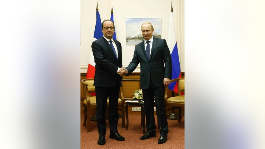 Russian President Vladimir Putin, right, and his French counterpart Francois Hollande shake hands during their meeting at Moscow's Vnukovo airport, Saturday, Dec. 6, 2014. The French leader met with Vladimir Putin at a Moscow airport on Saturday in an unexpected stopover visit, as he traveled from neighboring Kazakhstan back to Paris. (AP Photo/Maxim Zmeyev, Pool)