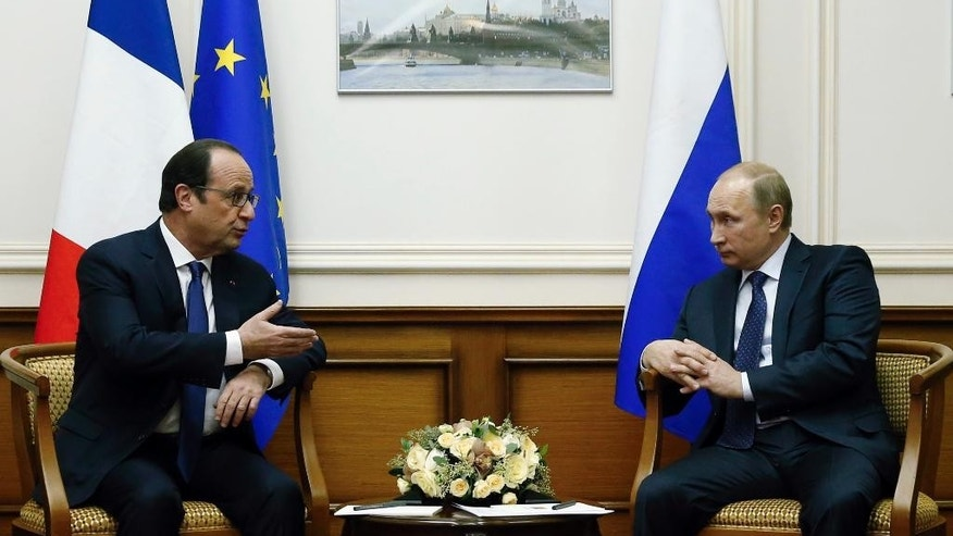 Russian President Vladimir Putin, right, and French President Francois Hollande speak during their meeting at Moscow's Vnukovo airport, Saturday, Dec. 6, 2014. French President Francois Hollande met with Russia's Vladimir Putin during an impromptu visit to Moscow on Saturday, as tensions remain high over the ongoing conflict in east Ukraine and France's decision to suspend the delivery of two warships to Moscow.  (AP Photo/Maxim Zmeyev, Pool)