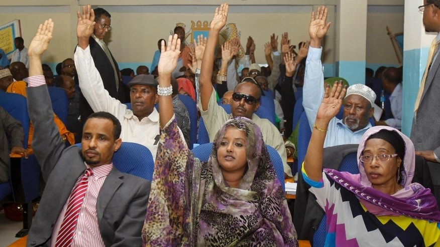 Somali lawmakers raise their hands to vote during a parliament session to impeach Somali Prime Minister Abdiweli Sheikh Ahmed, who lost the no-confidence vote in Mogadishu, Somalia, Saturday, Dec. 6, 2014. The speaker of Somalia's parliament says that the body of legislators has voted to oust the country's prime minister Abdiweli Sheikh Ahmed from office, with the vote taking place after several recent rowdy sessions of parliament over the issue. (AP Photo/Farah Abdi Warsameh)
